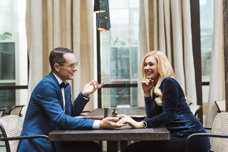 side view of happy adult couple having date at restaurant and holding hands