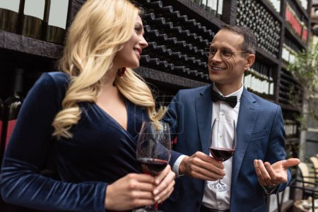attractive adult couple drinking wine in front of wine storage shelves