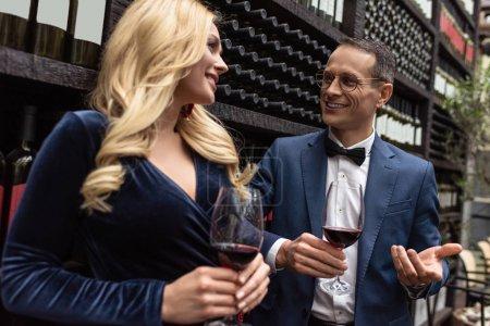 Photo pour Attrayant couple adulte buvant du vin devant les étagères de stockage de vin - image libre de droit