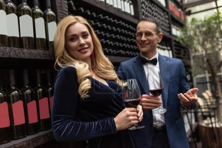 happy adult couple drinking wine in front of wine storage shelves