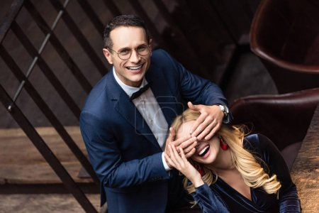 happy adult man covering eyes of his girlfriend