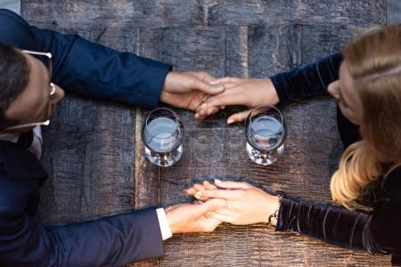 top view of adult couple holding hands at restaurant while drinking wine
