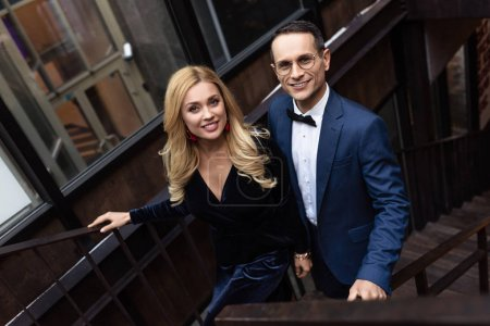 high angle view of adult couple in stylish clothing going up stairs