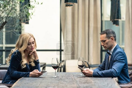 side view of bored adult couple using smartphones at restaurant