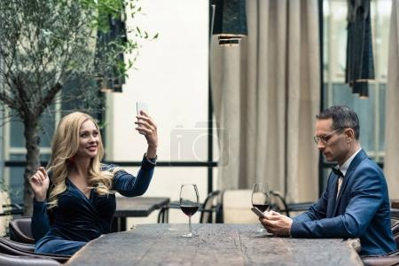 side view of unhappy adult couple using smartphones at restaurant