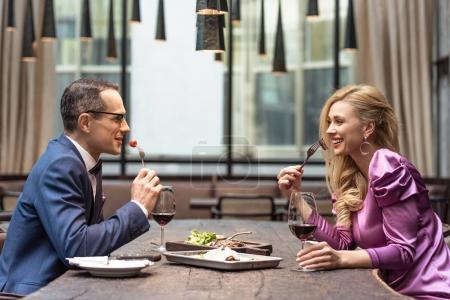 Photo pour Vue latérale de beau couple adulte mangeant au restaurant de luxe - image libre de droit