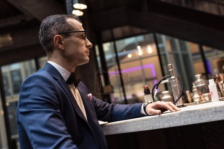 handsome man in stylish suit sitting at bar counter of luxury restaurant