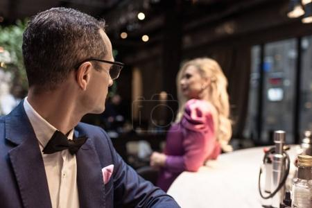 handsome adult man looking at woman leaning at bar counter