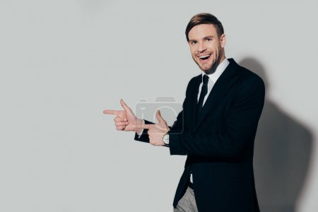 Stylish businessman in suit pointing on white background