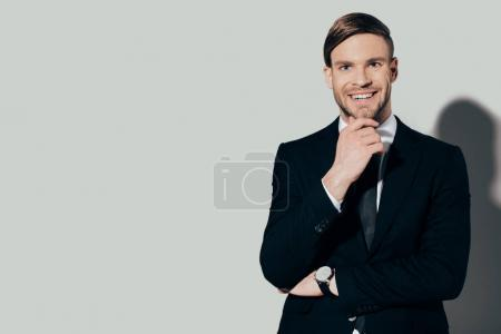 Young smiling businessman in suit with hand on chin on white background