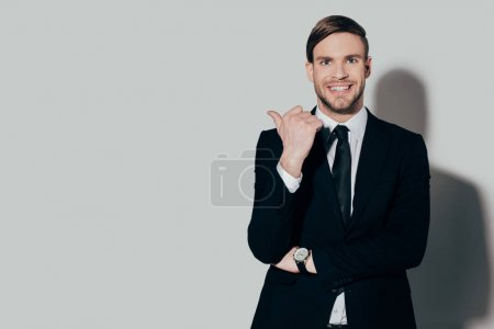 Stylish businessman in suit smiling and pointing on white background