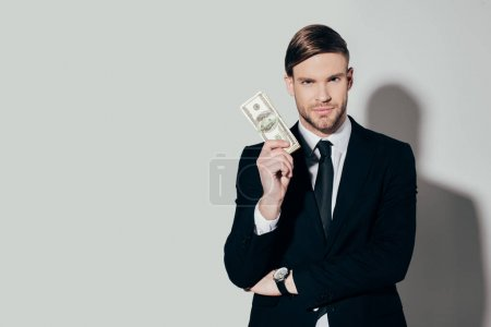 Young confident businessman in suit showing dollar banknote looking at camera on white background