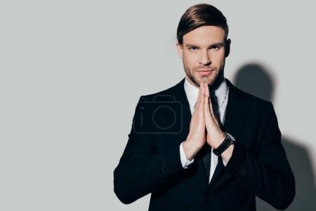 Photo pour Jeune homme d'affaires confiant avec geste de prière sur fond blanc regardant la caméra - image libre de droit