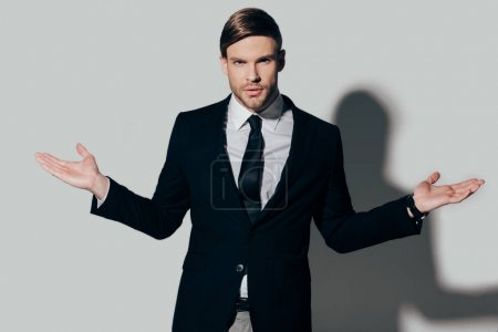 Young businessman in suit showing shrug gesture on white background