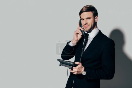 Young confident businessman in suit talking on the phone on white background
