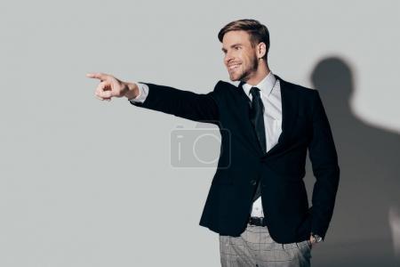 Photo pour Homme d'affaires excité en costume pointant sur fond blanc - image libre de droit