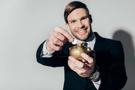 Young confident businessman in suit putting coin in golden piggy bank on white background