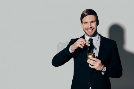 Smiling businessman in suit putting coin in golden piggy bank on white background
