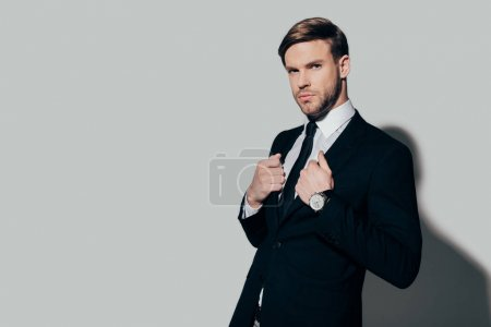 Young stylish confident businessman in suit on white background