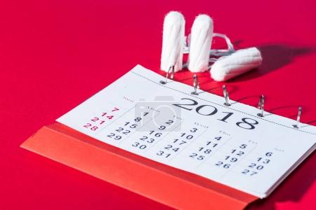 cotton feminine tampons and calendar on red