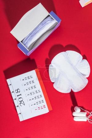 top view of menstrual tampons, daily liners and calendar on red