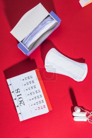 top view of tampons, daily liners and calendar on red