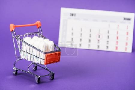 tampons in small shopping cart and calendar on purple