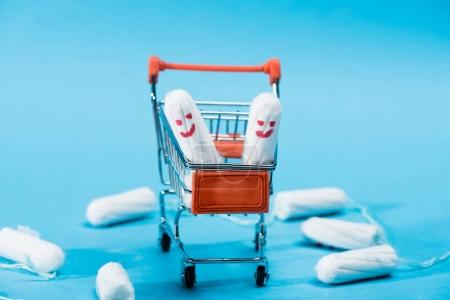 Photo for Tampons with happy smileys in small shopping cart on blue - Royalty Free Image