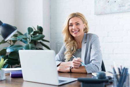 Photo for Smiling businesswoman looking at camera in office - Royalty Free Image