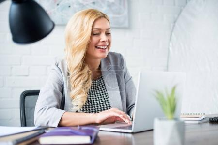 smiling businesswoman using laptop at work