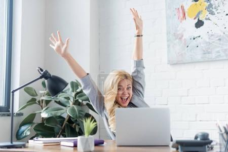 happy businesswoman screaming with hands up and looking at laptop