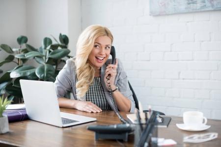 Photo pour Smiling businesswoman parler par téléphone au bureau - image libre de droit