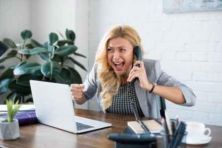 excited businesswoman talking by telephone in office and showing yes gesture