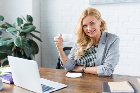 happy businesswoman holding cup of coffee in office and looking at camera