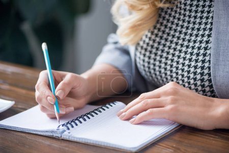 cropped image of businesswoman writing something to notebook with pencil