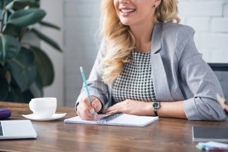 cropped image of smiling businesswoman writing something to notebook with pencil in office
