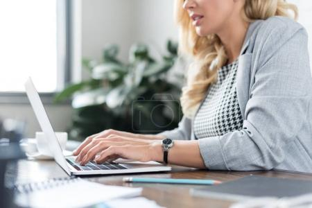 Photo for Cropped image of businesswoman using laptop at work - Royalty Free Image