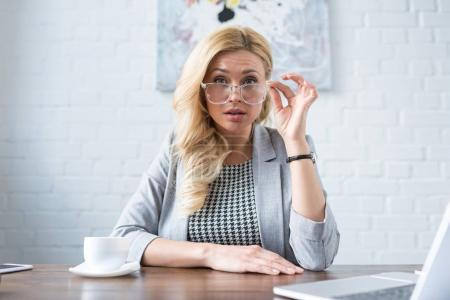 businesswoman looking at camera above glasses