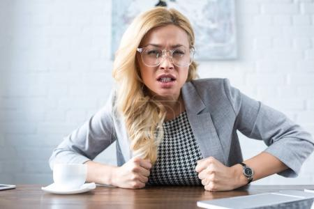 irritated businesswoman with fists looking at camera