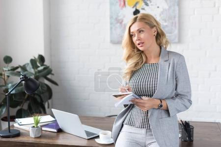 Photo for Thoughtful businesswoman standing with pencil and notebook - Royalty Free Image