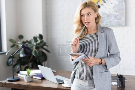 businesswoman biting pencil and looking away