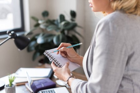 cropped image of businesswoman writing something in notebook at office