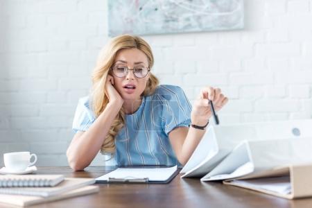 Photo pour Femme d'affaires fatigué, assis à table avec les dossiers et documents - image libre de droit