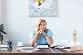 pensive businesswoman sitting at table and looking up
