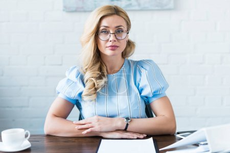 Photo for Attractive businesswoman sitting at table in office and looking at camera - Royalty Free Image
