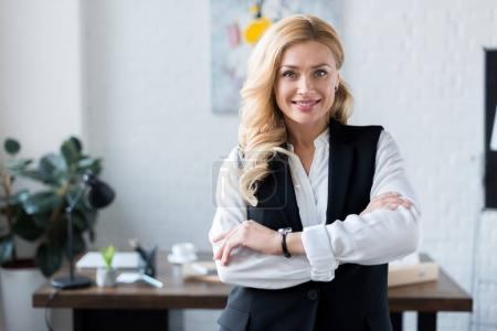 Photo for Smiling businesswoman with crossed arms looking at camera - Royalty Free Image