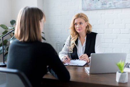 beautiful businesswoman talking with coworker at table in office