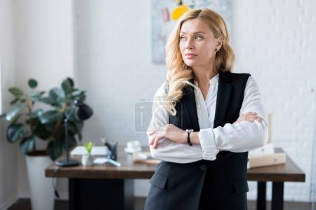 Photo for Beautiful businesswoman with crossed arms looking away - Royalty Free Image