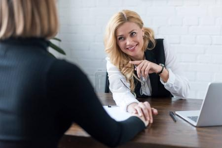 smiling businesswoman palming coworker hand in office