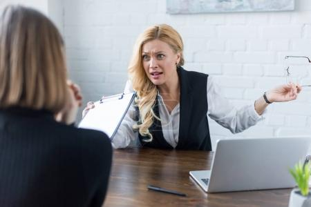 angry businesswoman gesturing while talking with coworker in office